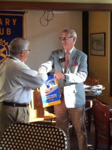 District Governor Lance Young presents Club president with a Rotary Banner